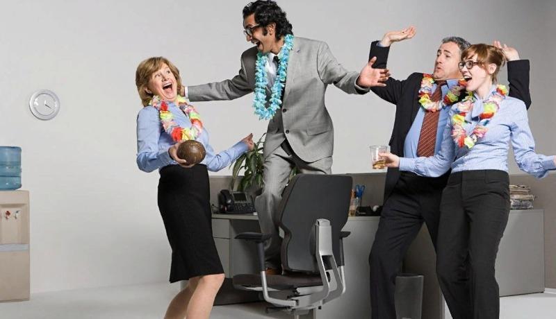 Работники офиса танцуют в гавайских ожерельях